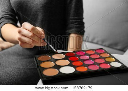 Female visagiste using palette for make up, closeup