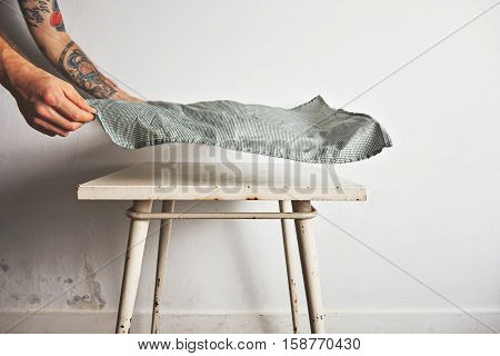 Man with tattooed arms puts a traditional green and white tablecloth over a small white old table with rust stains