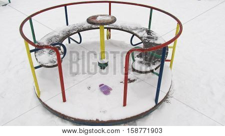 Lonely children's carousel in winter, forgotten mitten in the snow