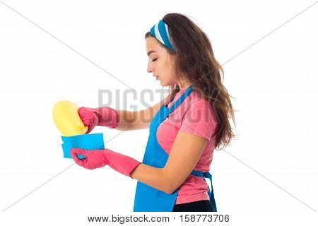 young cute maid woman in an apron with cleansers isolated on white background