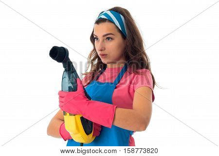 serious maid woman in an apron with cleansers isolated on white background