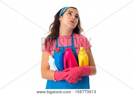 portrait of sad young maid woman in an apron with cleansers isolated on white background