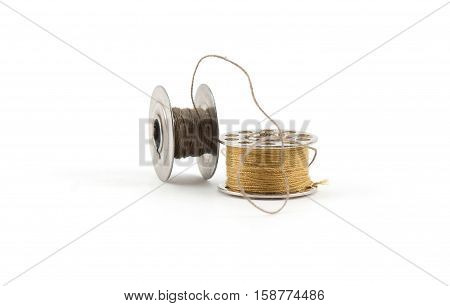 Sewing thread bobbins and needles isolated on white background