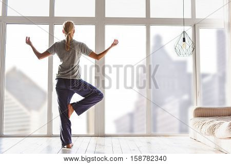 Healthy girl is doing yoga in living room. She is standing in one leg and raising arms up. Lady is looking through window with peacefulness