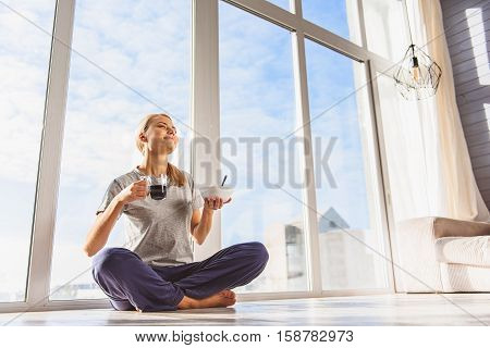 Meeting new day. Happy girl is eating cornflakes and drinking coffee with enjoyment. She is sitting on flooring near window and smiling. Her eyes are closed with pleasure