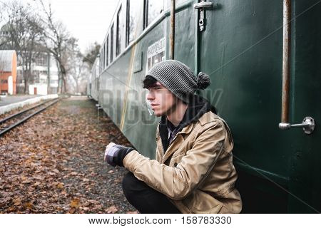A young guy in a jacket with a backpack near train.