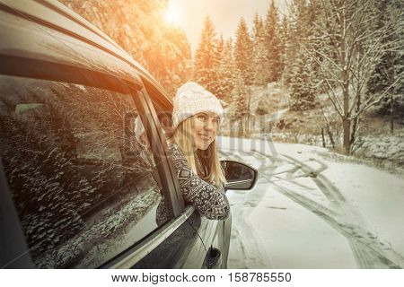 Woman at winter time. Yoyng female looking in window of her black car at snowly winter day.