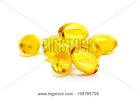 Fish oil supplement capsules selective focus in front object isolated on white background