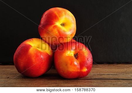Nectarines isolated on a wooden and black background