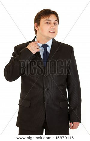 Stressful businessman pulling collar of his shirt isolated on white