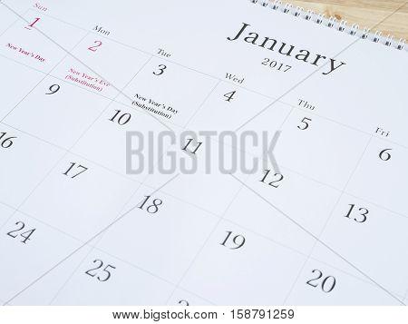 January on white calendar page desk calendar on wood background (Selective focus)