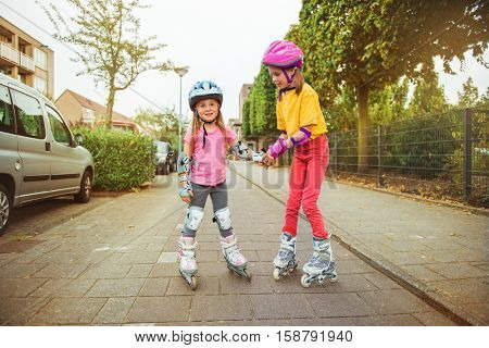 Two kids trying new activity -  inline roller skating