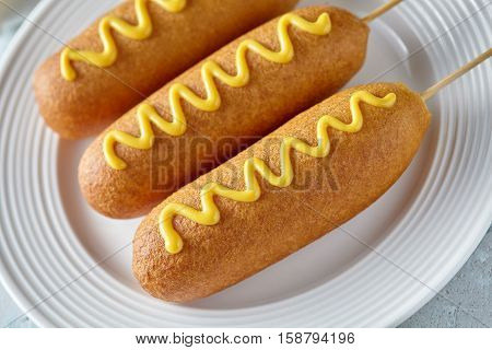 Corn dog traditional American food fried hotdog meat wiener with mustard on top snack treat in a layer of cornmeal batter on stick unhealthy eating on rustic table.