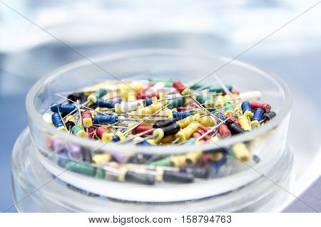 Dental tools in the glass round box. Dental instruments - k-files. Close-up dentist tools capture.