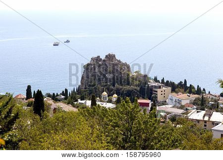 Gurzuf, Crimea - September 7, 2016: Rocky Beach with a protruding rock domes of churches and residential buildings located among different vegetation. Rock of Chaliapin, Church of the Assumption of the Blessed Virgin look with Bolgatura Mountains in Gurzu