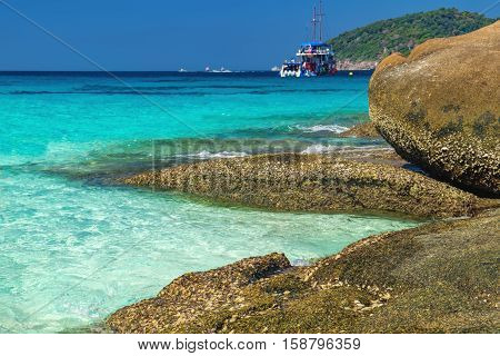 Foamy waves on the Koh Similan in Similan National park, Andaman Sea, Thailand. Beautiful landscape with the rock and tourist boats.