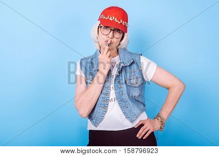 Feel brutal. Attractive senior woman putting arm on her hip and kissing middle finger while standing against isolated blue background.