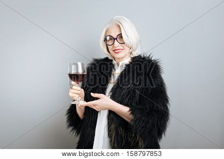 Pleasant time. Senior elegant pretty woman smiling and holding wineglass while standing against isolated gray background.