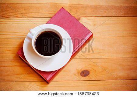 Coffee cup and book on wooden background. Top view
