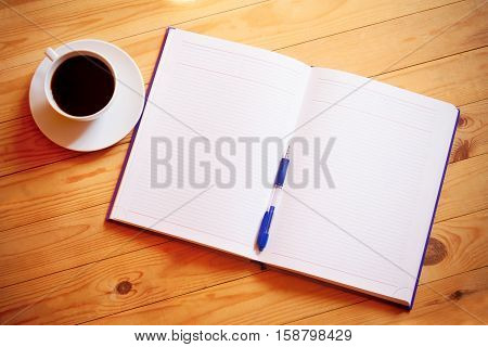 Cup of coffee pen opened organizer on wooden background