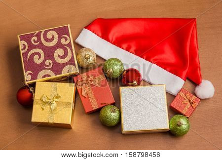 Santa hat gift boxes and christmas balls on wooden background