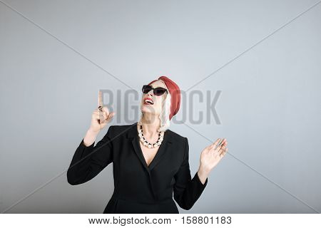 Just look. Surprised beautiful woman pointing on stare and opening mouth while standing against isolated gray background.