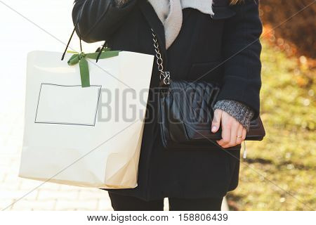 A woman in a black coat with a bag and shopping pack. Stylish Girl. Black leather bag and a gray coat. Autumn clothes. Winter clothes. Street fashion, street look.