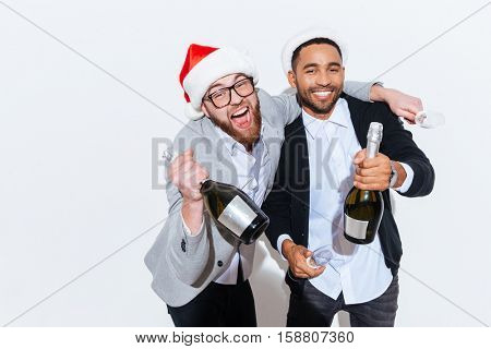Two cheerful young men in santa claus hats with champagne celebrating new year over white background