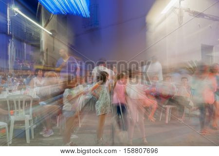 Alcalali, Spain - August 29, 2016; Long exposure people in blurred motion in sStreets of Alcalali holiday festival night scenes
