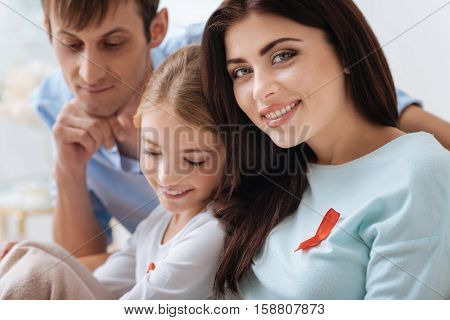 Pleasant moments. Beautiful delighted nice woman sitting near her family members and smiling while wearing a symbol of AIDS campaign