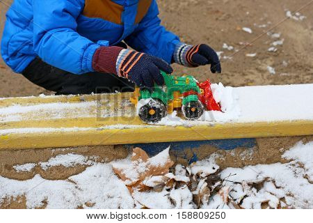 Part of the image of a small child who sits between the first snow and sand and plays with red toy construction equipment. Visible hand dressed in a blue jacket black pants and boots.
