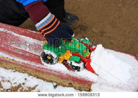 Part of the image of a small child who sits between the first snow and sand and plays with red toy construction equipment. Visible hand dressed in a blue jacket.