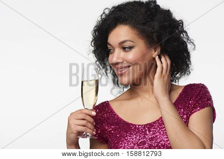 Party, drinks, holidays and celebration concept. Closeup smiling woman in sequined dress with glass of champagne looking to the side at blank copy space