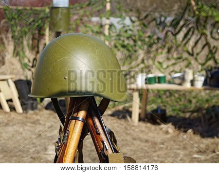 Protective helmet of a soldier hanging on military rifles.
