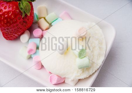 Ice cream sundae, strawberry and candies on a table