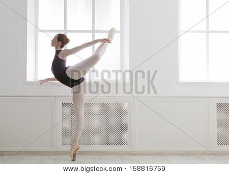 Classical Ballet dancer side view. Beautiful graceful ballerine in black practice arabesque ballet position near large window in light hall. Ballet class training, high-key soft toning.