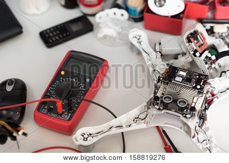 Testing process. Close up of electronic tester and motherboard lying on a table with other equipment.