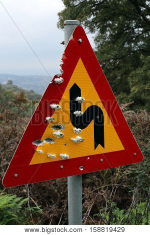 A new hazard warning sign on a mountain road in Crete, Greece, that has been peppered with bullets by gun-crazy locals. Road signs are frequently used for target practice in rural areas of the island.