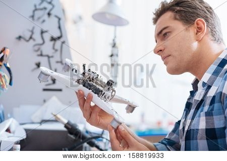 Test it. Concentrated young handsome man holding drone detail while discovering it and working as a repairman.