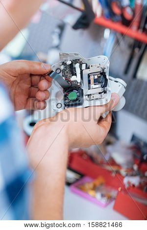 Discovering mechanism. close up of young mans hands holding drone camera while controlling the chips and working as a repairman.