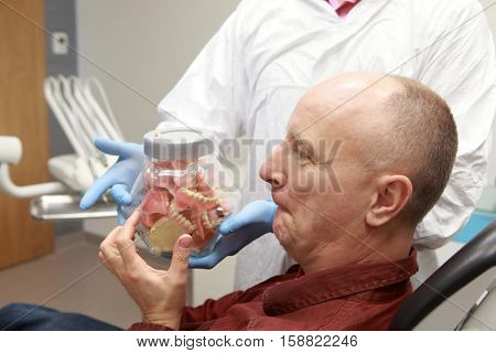 mature  toothless patient selecting new set of dentures