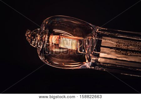 Closeup of a halogen bulb made of of glass the volfram wire is barely glowing.