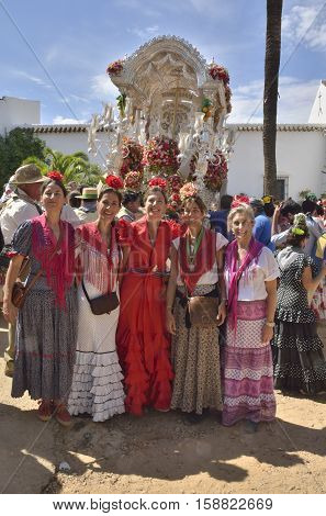 Huelva, Spain - June 5, 2014: Women with typical dresses in way of pilgrimage El Rocio in front of the the pennant of the religious brotherhood in the countryside of Huelva Spain