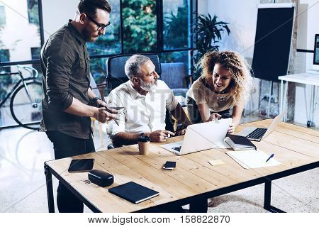 Young team of coworkers making great work discussion in modern coworking office.Bearded man talking with colleagues about new startup project.Business people brainstorm concept.Horizontal, blurred