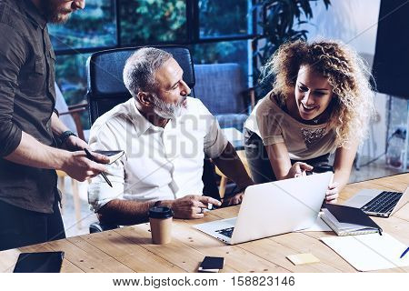 Young team of coworkers making great work discussion in modern coworking office.Bearded man talking with colleagues about new startup project.Business people brainstorm concept.Horizontal close-up