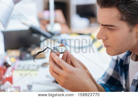 Keep it under control. Handsome serious young man discovering a chip of drone while repairing it and sitting in a workroom.