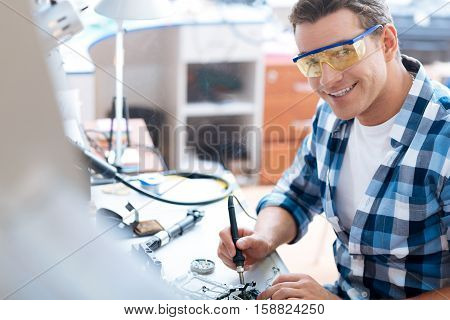 Enjoy hard work. Joyful young concentrated man soldering drone details attentively and using soldering iron while working.