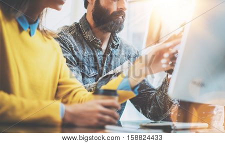 Business people brainstorming concept.Young team of coworkers working together in modern coworking office.Bearded man talking with colleague about new startup project.Horizontal, flare effect