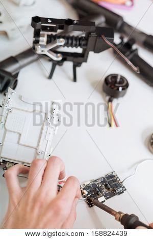 Look at this process.Top view of mans hands soldering drone chips attentively and using soldering iron while enjoying hobby