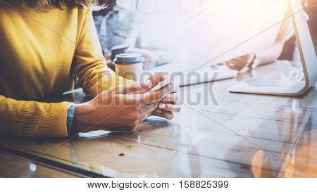 Teamwork concept. Young team of coworkers working together in modern coworking office.Woman using in hands smartphone. Man working on desktop computer.Horizontal, flare effect